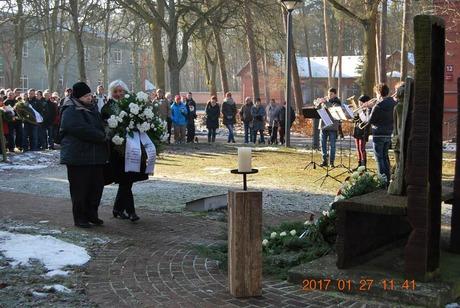 Bild: ABiMV-DL. Barbara Mortensen und Heidrun Lips legen im Gedenken an die Opfer einen Kranz am Mahnmal nieder.